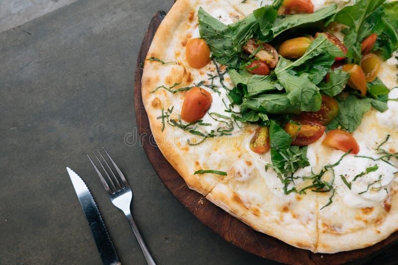 Verse Italiaanse pizza met tomaten, kaas, basilicum op zwarte steenachtergrond met mes en de ruimte van het vorkexemplaar Eigenge stock afbeelding
