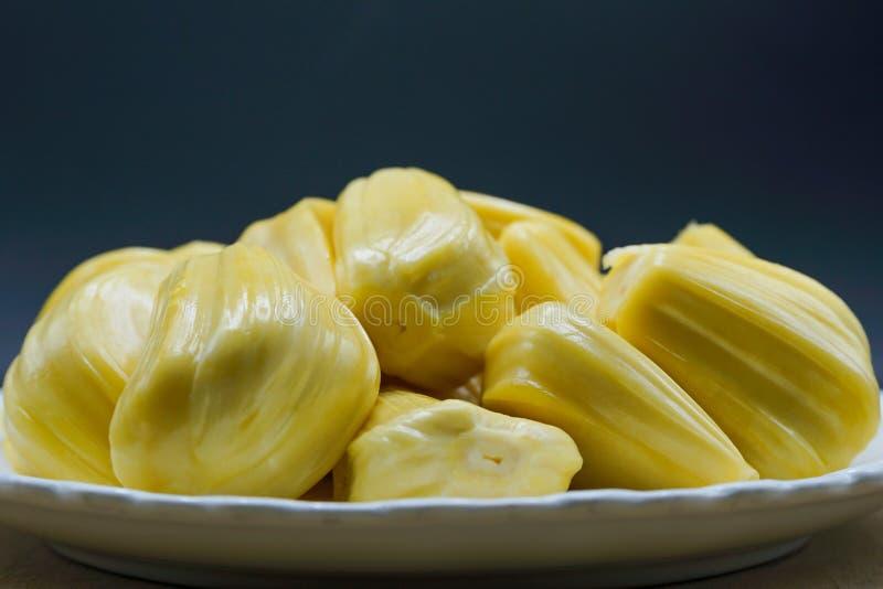 Verse jackfruitplakken op een witte plaat zoete gele rijpe jackfruit Vegetariër, veganist, ruw voedsel Exotisch tropisch fruit -  royalty-vrije stock afbeeldingen