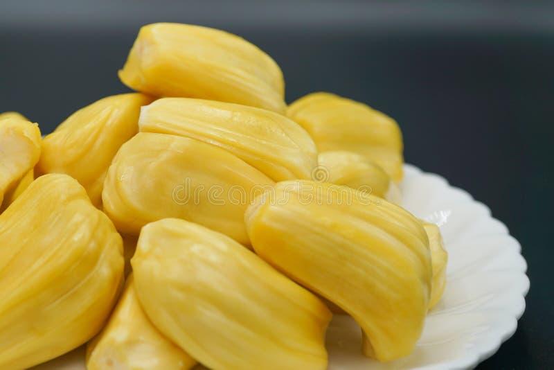Verse jackfruitplakken op een witte plaat zoete gele rijpe jackfruit Vegetariër, veganist, ruw voedsel Exotisch tropisch fruit -  stock foto
