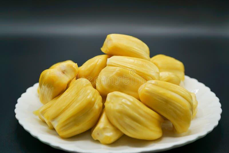 Verse jackfruitplakken op een witte plaat zoete gele rijpe jackfruit Vegetariër, veganist, ruw voedsel Exotisch tropisch fruit -  royalty-vrije stock afbeelding