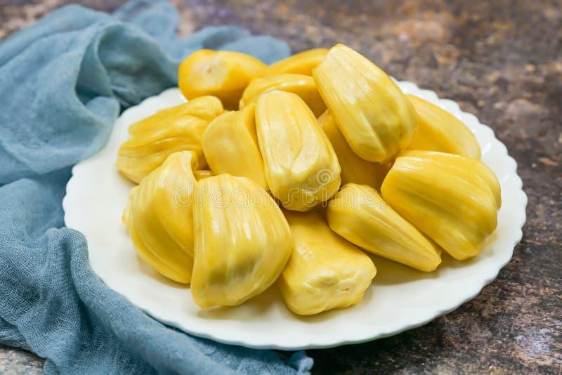 Verse jackfruitplakken op een witte plaat zoete gele rijpe jackfruit Vegetariër, veganist, ruw voedsel Exotisch tropisch fruit -  royalty-vrije stock foto