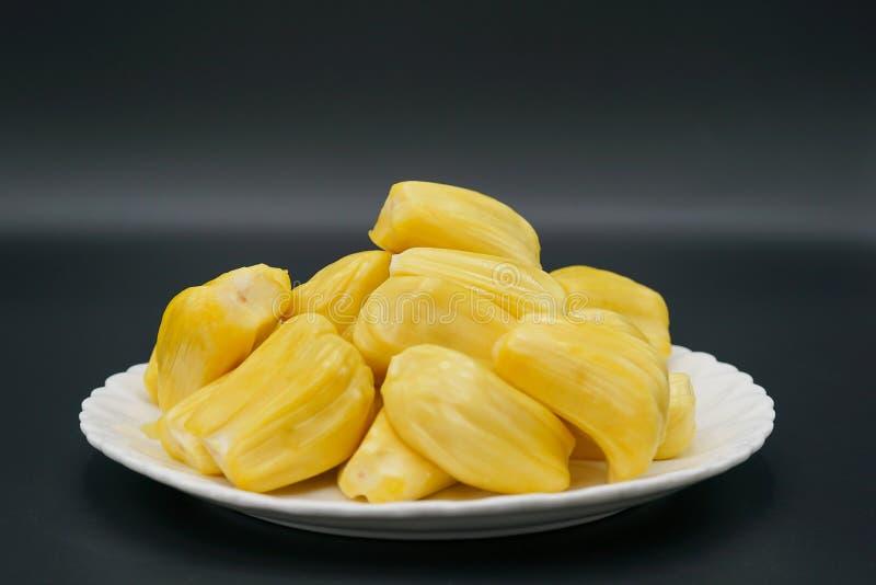 Verse jackfruitplakken op een witte plaat zoete gele rijpe jackfruit Vegetariër, veganist, ruw voedsel Exotisch tropisch fruit -  stock fotografie