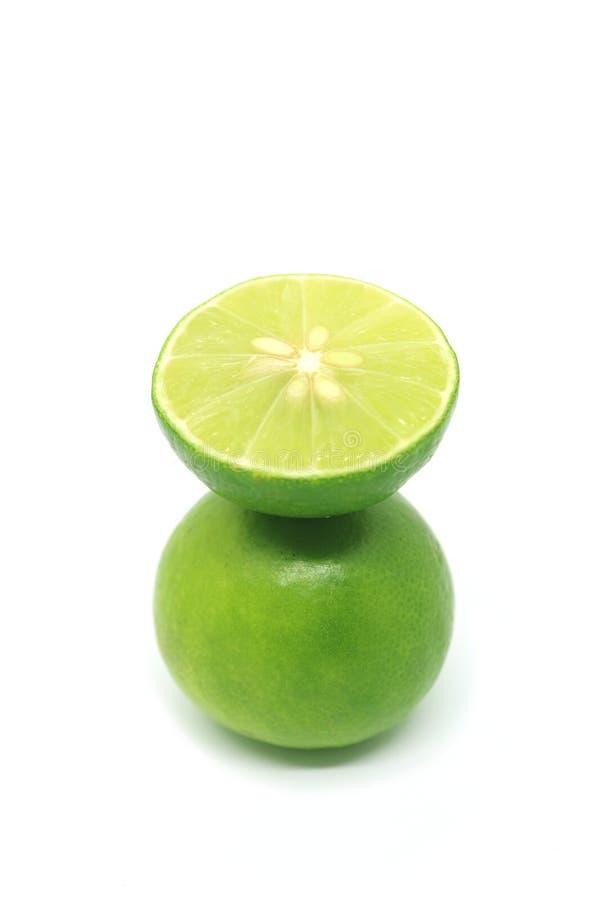 Verse kalk in dwarsdoorsnede gezet over het gehele fruit dat op witte achtergrond wordt geïsoleerd stock foto