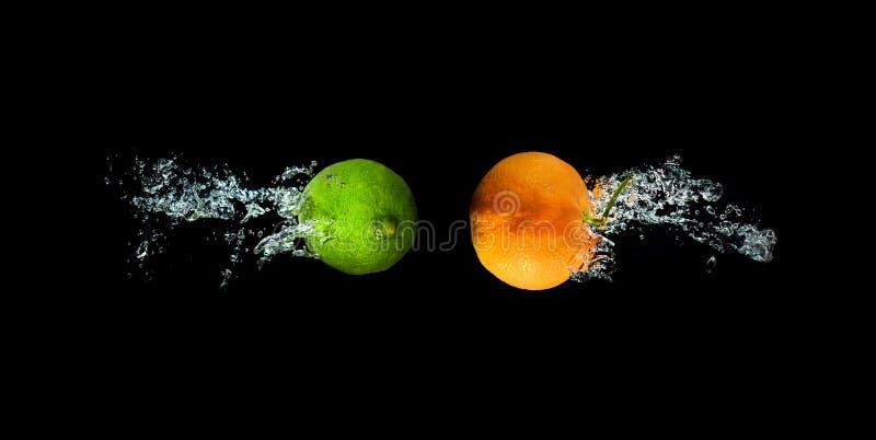 Verse kalk en sinaasappel in water met de plons ISO van het luchtbellenwater stock foto's