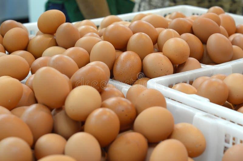 Verse kippeneieren in plastic mand bij markt stock afbeelding