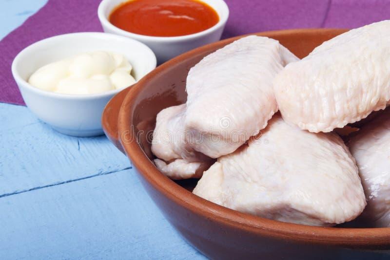 Verse kippenvleugels van binnenlandse vogel in ceramische schotels voor het koken van een dieetschotel Ruimte voor ontwerp of tek royalty-vrije stock foto's