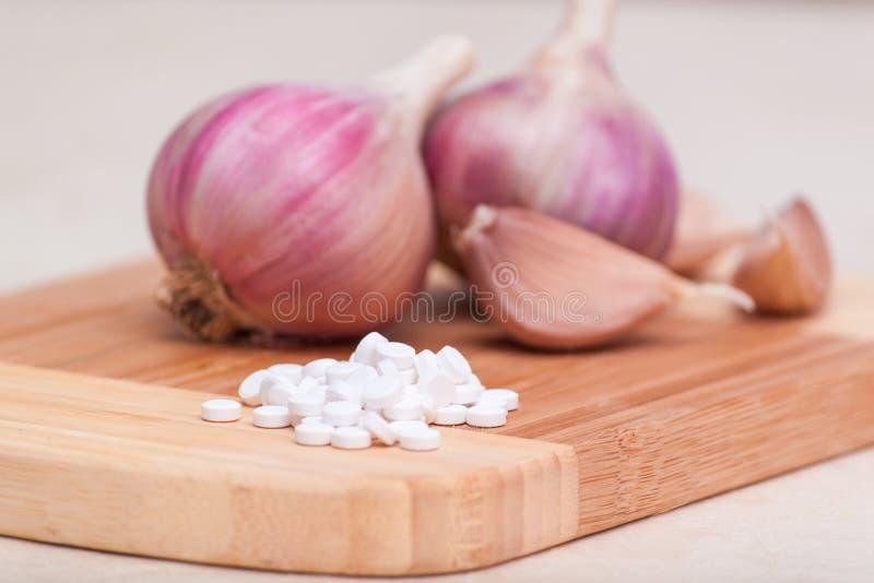 Verse knoflookbollen en knoflookkruidnagels op een houten scherpe raad Concepten alternatieve geneeskunde, dieetsupplementen of p stock afbeelding