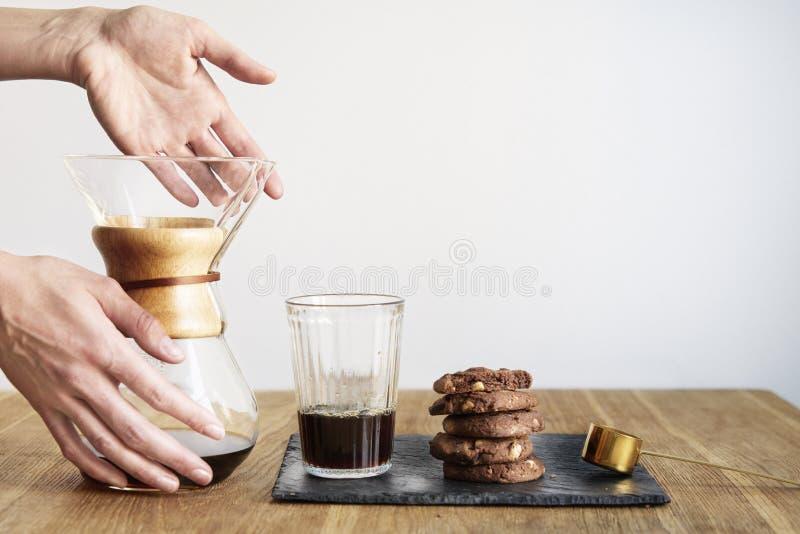 Verse koffie in Chemex, zoet browniekoekje op houten lijst Mooie vrouwen` s handen die van glaskom gieten Witte muur erachter stock foto