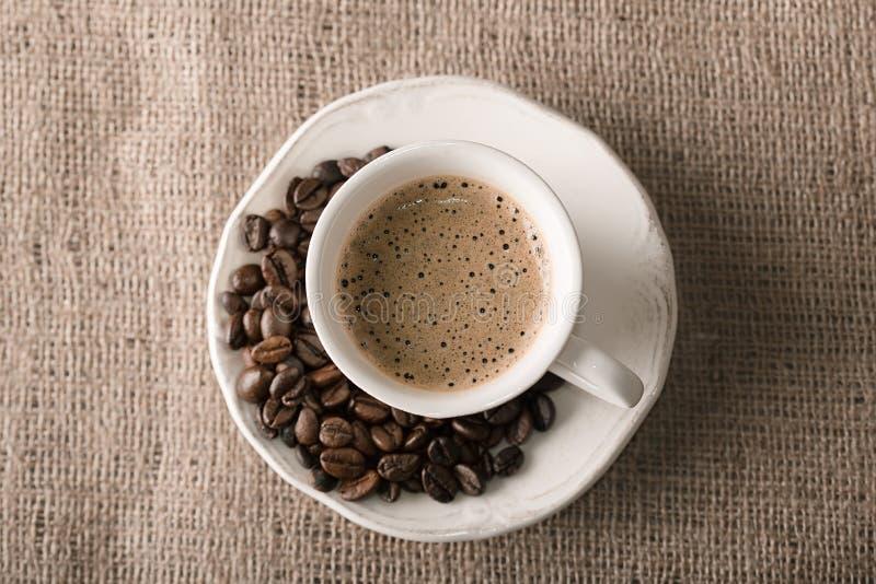 Verse koffie en koffiebonen op jute stock afbeeldingen
