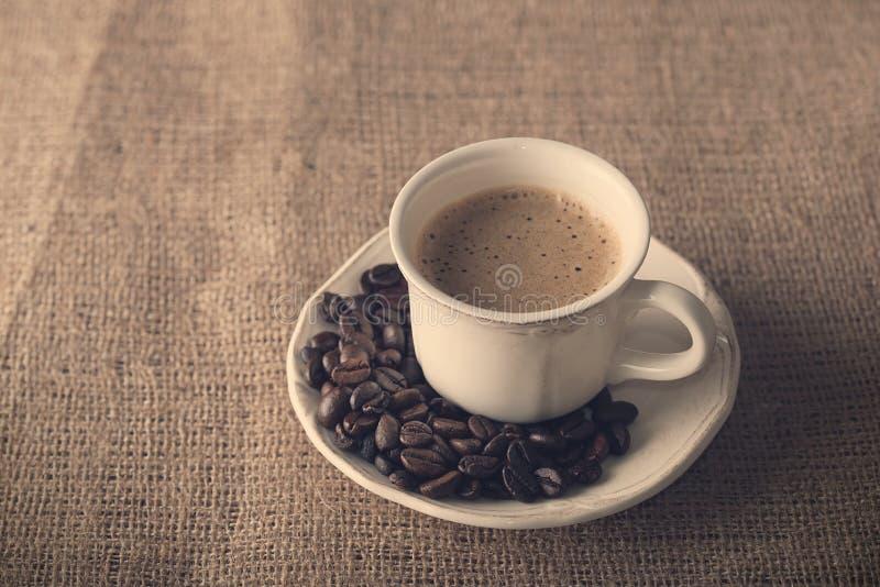 Verse koffie en koffiebonen op jute royalty-vrije stock fotografie