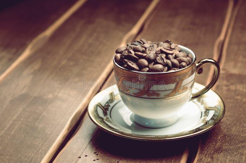 Verse koffiebonen kop op een houten achtergrond stock afbeeldingen