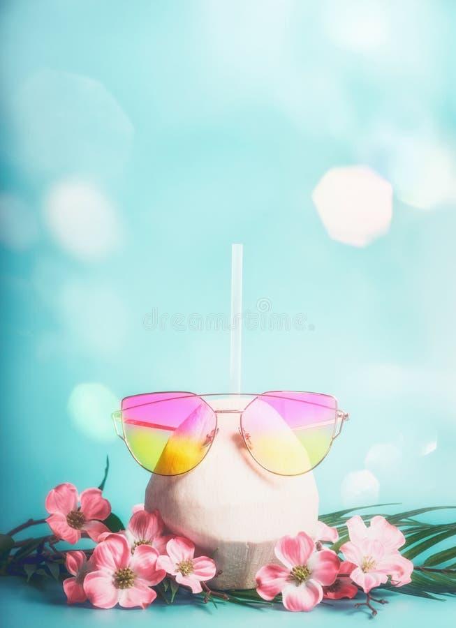 Verse kokosnotencocktail met roze zonnebril met tropische bladeren en bloemen bij blauwe achtergrond met bokeh Tropische vakantie royalty-vrije stock foto's