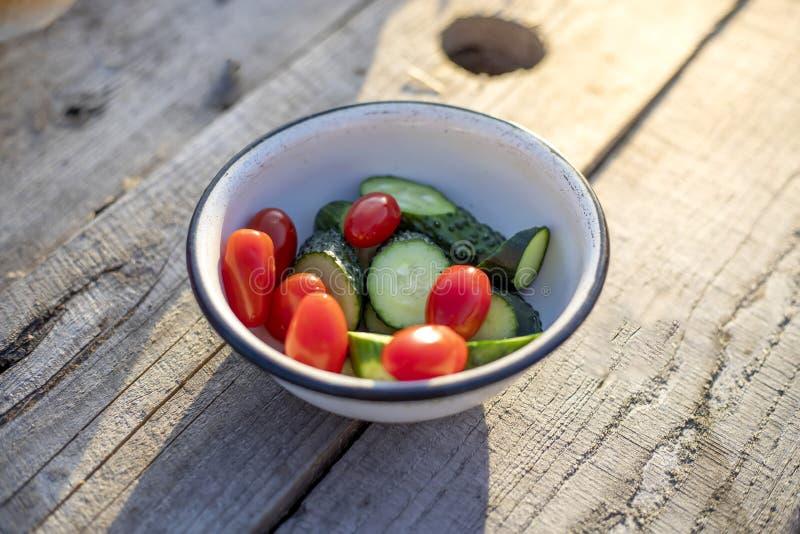 Verse komkommers en tomaten in een witte plaat op een houten tafel, bovenaanzicht stock foto