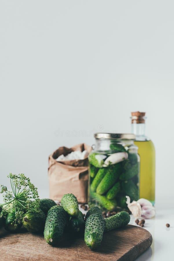 verse komkommers op scherpe raad op lijst met bewaarde komkommers in glaskruik royalty-vrije stock afbeeldingen