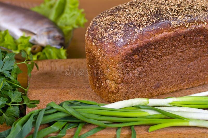 Verse kruiden traditionele brood en vissen op een houten raad stock fotografie