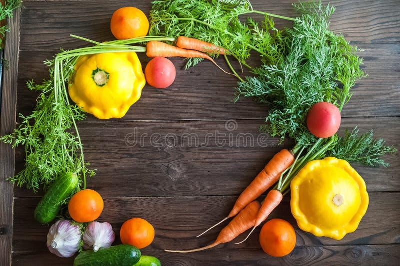 Verse landbouwbedrijfgroenten op de achtergrond van een donkere geweven houten lijst Van het groentenclose-up en exemplaar ruimte stock afbeeldingen