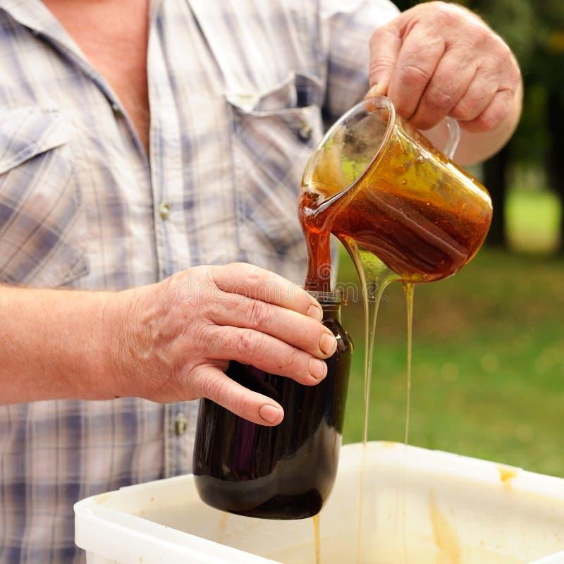Verse landbouwers organische die honing in glaskruik wordt gegoten stock foto's