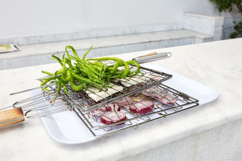 Verse lange groene paprika's, witte kaas en gesneden rode uien die tussen het net van de draadgrill op een dienblad worden geplaa stock foto
