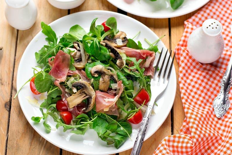 Verse lichte plantaardige salade met arugulasla, paddestoelen, kersentomaat en genezen ham royalty-vrije stock fotografie