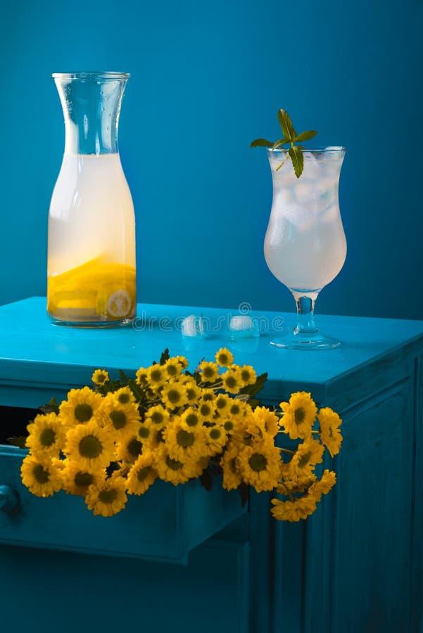 Verse limonade en gele bloemen in blauw decor royalty-vrije stock foto's