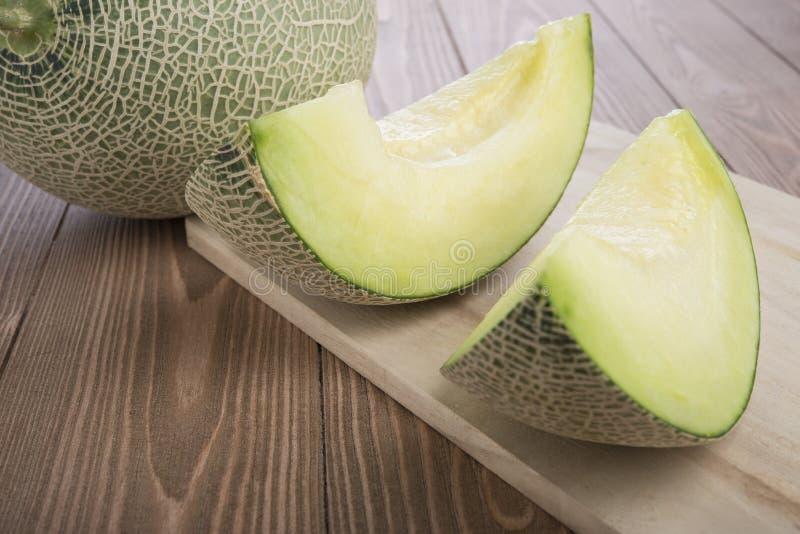 Verse meloenenkantaloep die op houten scherpe raad en houten achtergrond wordt gesneden royalty-vrije stock fotografie