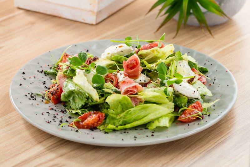Verse mengelingssalade met ham en droge tomaten op grijze plaat royalty-vrije stock afbeelding