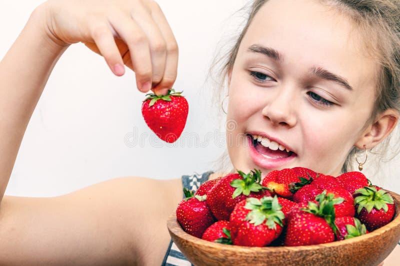 Verse mooie aardbeien in houten kom in een meisjeshand royalty-vrije stock fotografie