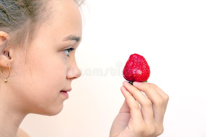 Verse mooie aardbeien in houten kom in een meisjeshand royalty-vrije stock foto's