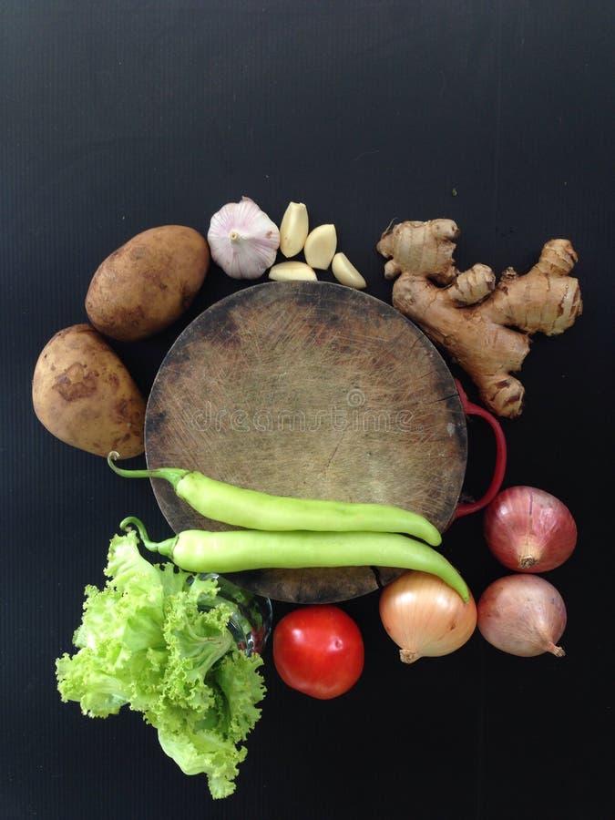 Verse natuurvoeding en groene paprika bij het hakken op zwarte achtergrond stock afbeelding