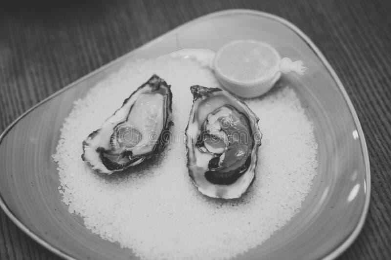 Verse oesterschaaldieren in luxerestaurant het eten van oester met citroen en verpletterd ijs gezonde delicatesse met Omega 3 royalty-vrije stock afbeeldingen
