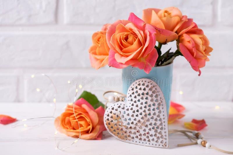 Verse oranje rozen in blauwe kop en decoratief hart stock afbeelding