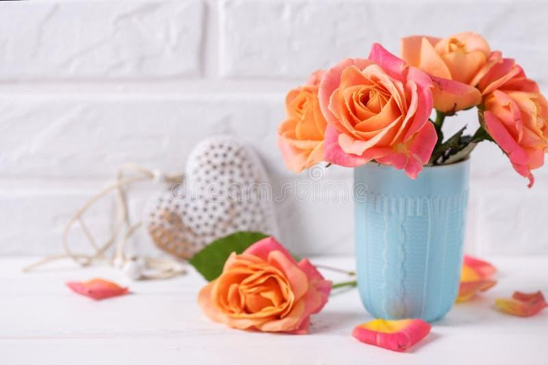 Verse oranje rozen in blauwe kop en decoratief hart op witte wo royalty-vrije stock fotografie