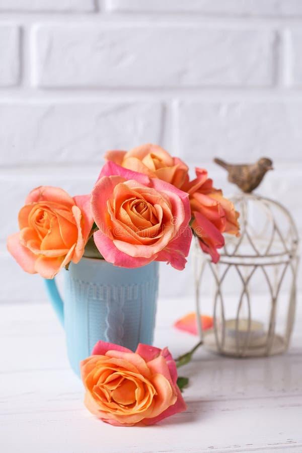 Verse oranje rozen in blauwe kop en kaars op witte houten rug royalty-vrije stock afbeeldingen