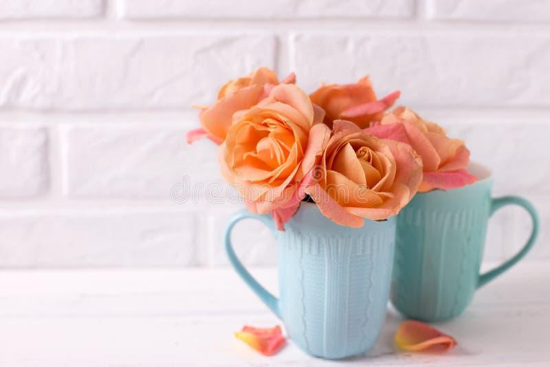 Verse oranje rozen in blauwe koppen stock afbeeldingen