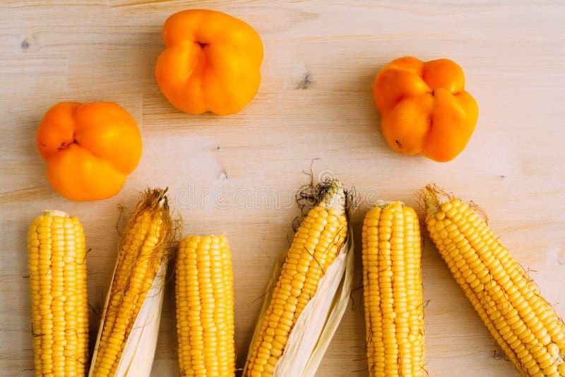 Verse organische gele suikermaïs en peper op houten lijst Hoogste mening stock foto's