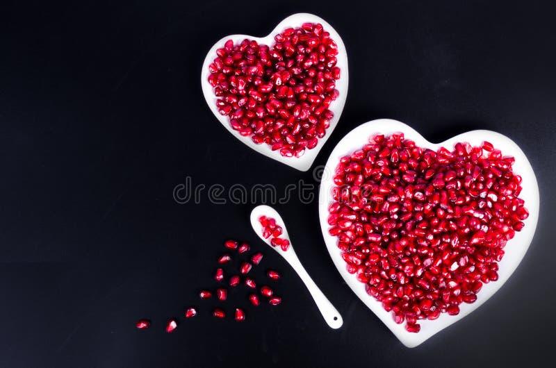 Verse organische granaatappelzaden in witte hart gevormde kom Vrije ruimte voor uw tekst royalty-vrije stock fotografie
