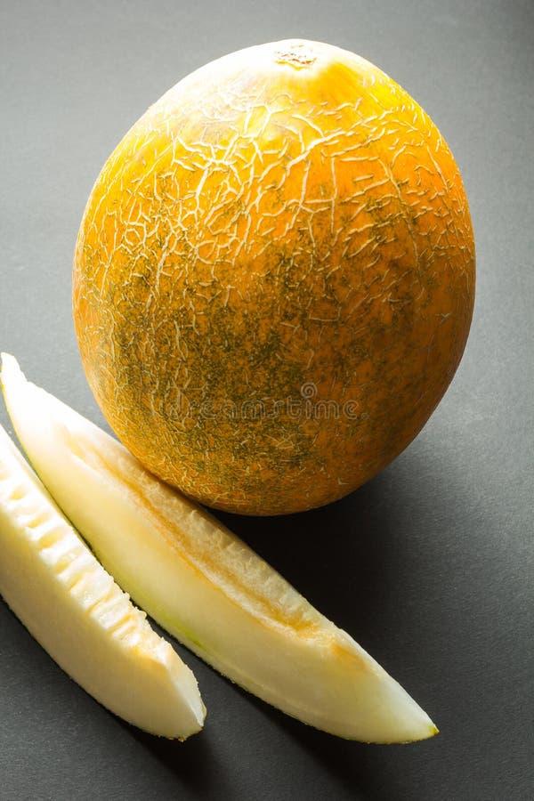 Verse organische kantaloepmeloenen en twee plakken op zwarte verticale achtergrond, royalty-vrije stock afbeelding