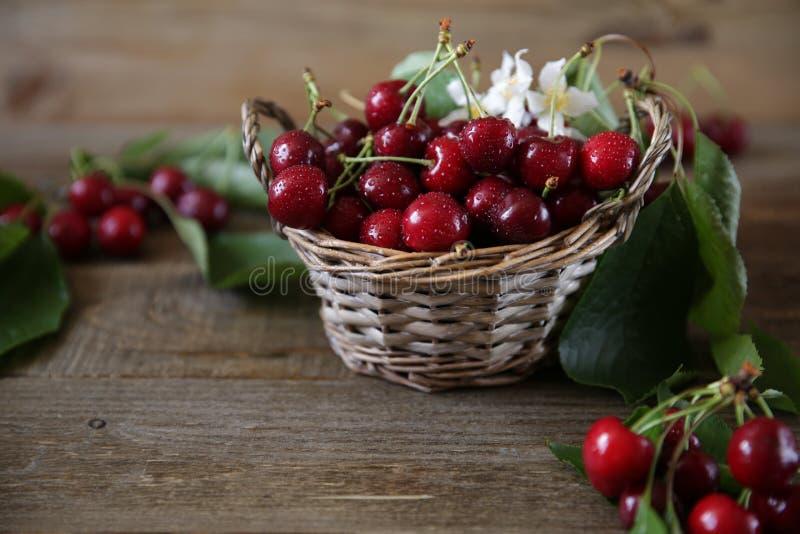 Verse organische kersen in een rieten mand met bladeren en witte bloemen op de houten rustieke achtergrond Gezond voedselconcept  royalty-vrije stock fotografie