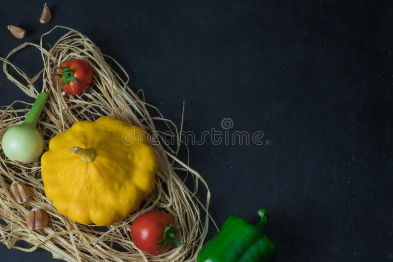 Verse organische seizoengebonden groenten - pompoen, pompoen, tomaat op zwart beton rustic stock fotografie