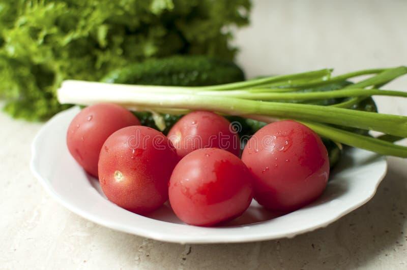 Verse organische tomaten en komkommers met groene uien op een witte plaat stock afbeeldingen