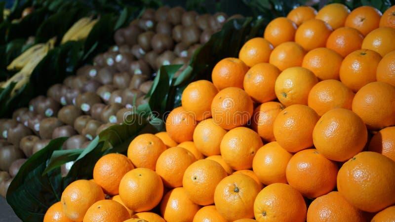 Verse organische vruchten sinaasappelen, kiwi, bananen op vertoning in landbouwersmarkt stock foto's