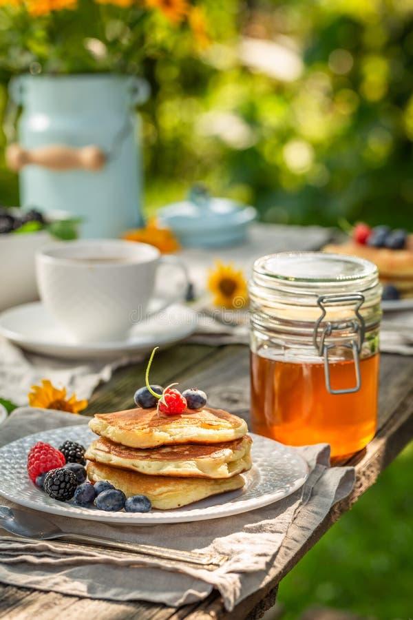 Verse pannekoeken met verse bosbessen en honing in de zomertuin stock afbeeldingen