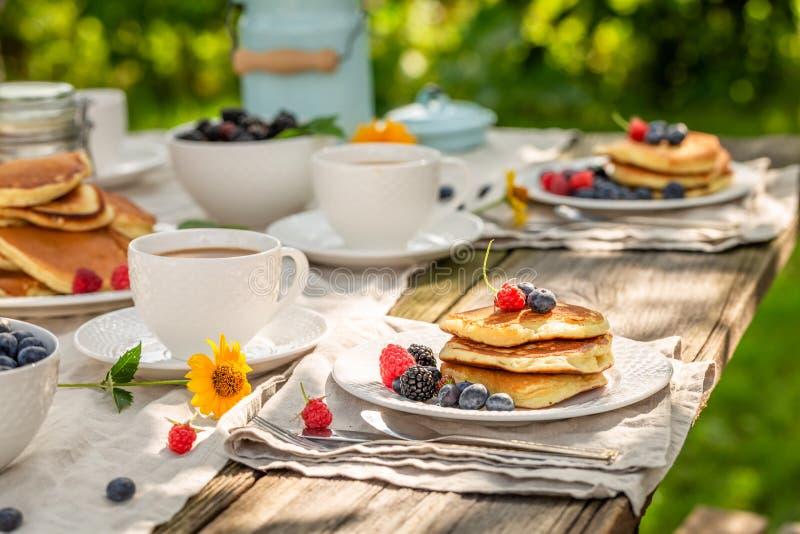 Verse pannekoeken voor ontbijt in de zomertuin stock foto's