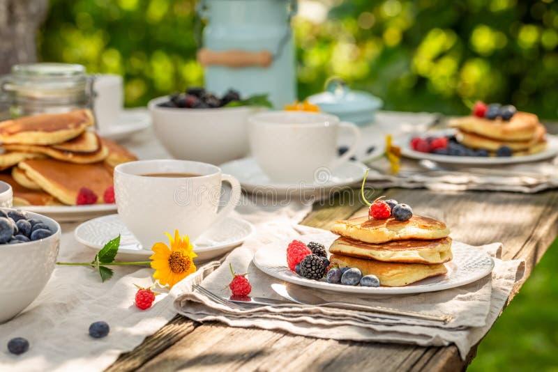 Verse pannekoeken voor ontbijt in zonnige tuin stock fotografie