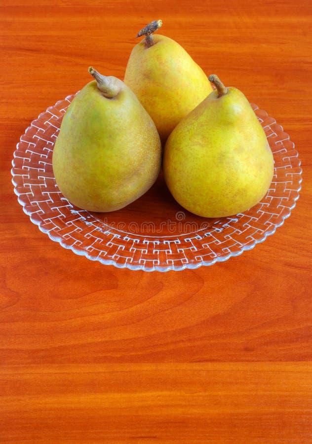 Verse peren in plaat op houten lijst stock fotografie