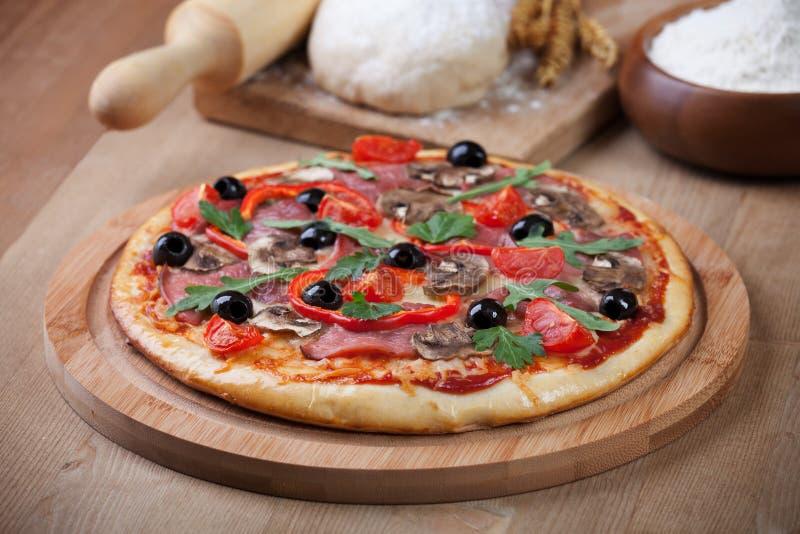 Verse pizza en ingrediënten aan boord stock afbeeldingen