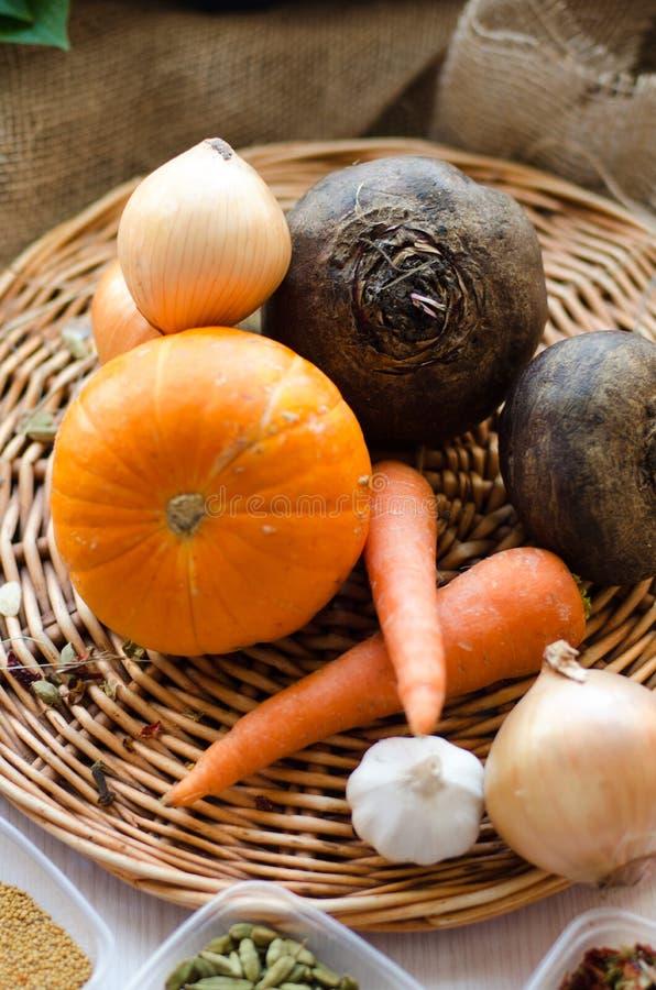 Verse product-groenten vegetables Wortelen, bieten, pompoen, ui, kruid op het rieten dienblad stock afbeeldingen
