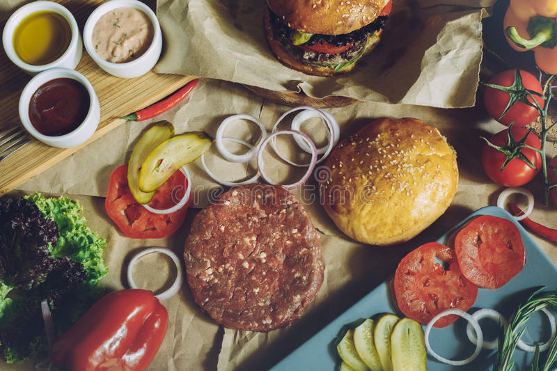 Verse producten en ingrediënten voor het maken van heerlijke hamburger op document oppervlakte eigengemaakt het Koken Concept stock afbeeldingen