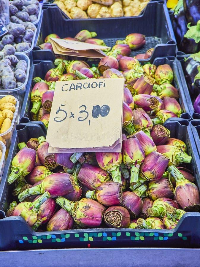 Verse purpere Artisjokken in een markt met een kartel in het Italiaans die de prijs tonen stock foto