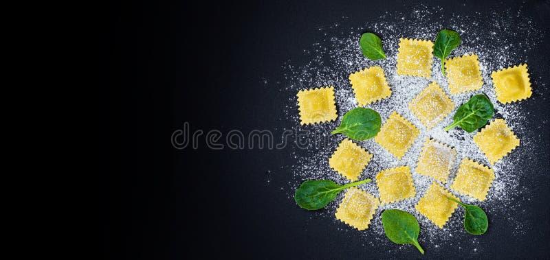 Verse raviolideegwaren met Spinazie, bloem en kruiden op donkere achtergrond, hoogste mening Italiaanse Raviolli De ruimte van he stock afbeelding